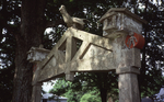 Top of Archway, detail of birdhouses, bird statue, and small decorative people, close up by James Smith Pierce