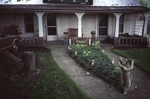 Front of home, porch art including columns and planters visible. Bird bath visible in foreground by James Smith Pierce