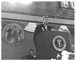 The President at the Podium with Elvira Jestrab in Back